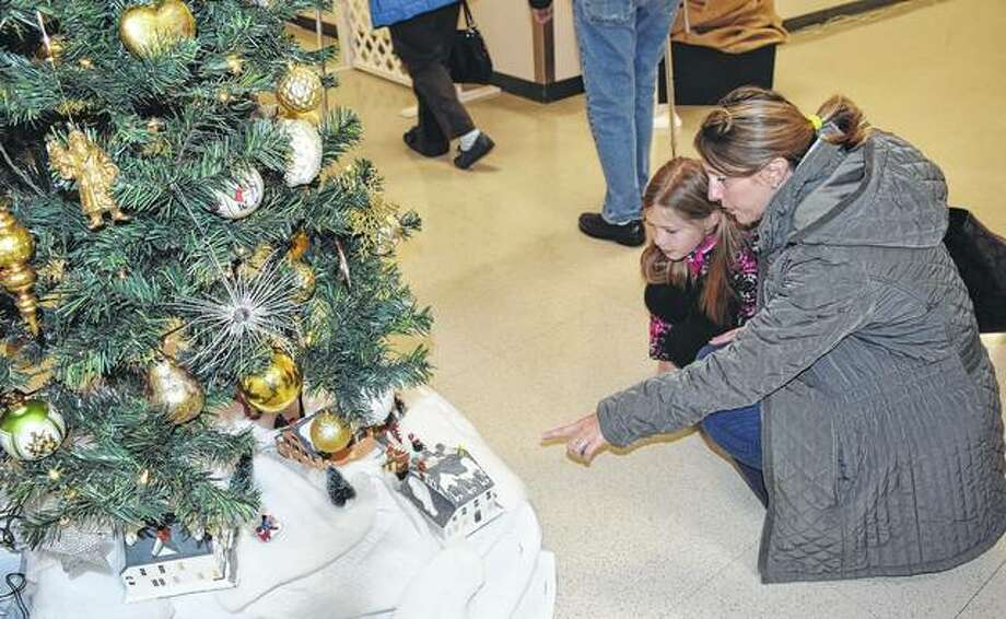 Faith Embley, 10, looks at Christmas trees Friday with her mother, Kelli Embley, during the Festival of Trees at Pathway Services Unlimited. The Festival of Trees will continue from 9 a.m. to 8 p.m. today and Sunday from 11 a.m. to 2 p.m. An auction will take place 2:30 p.m. Sunday. Photo: Samantha McDaniel-Ogletree | Journal-Courier