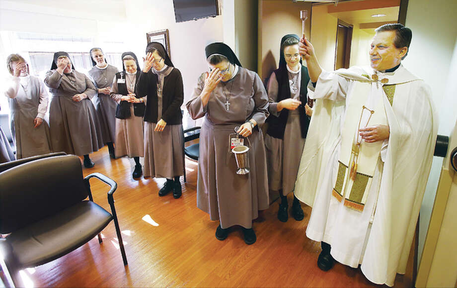 Fr. Steve Sotiroff, right, from the chapel and convent at OSF Saint Anthony's Hospital in Alton, sprinkles holy water to bless the $200,000 renovation of a suite at the Alton hospital Friday as Sisters of St. Francis of the Martyr St. George cross themselves. An existing suite at the hospital was completely renovated, including the lobby, office space and exam rooms.