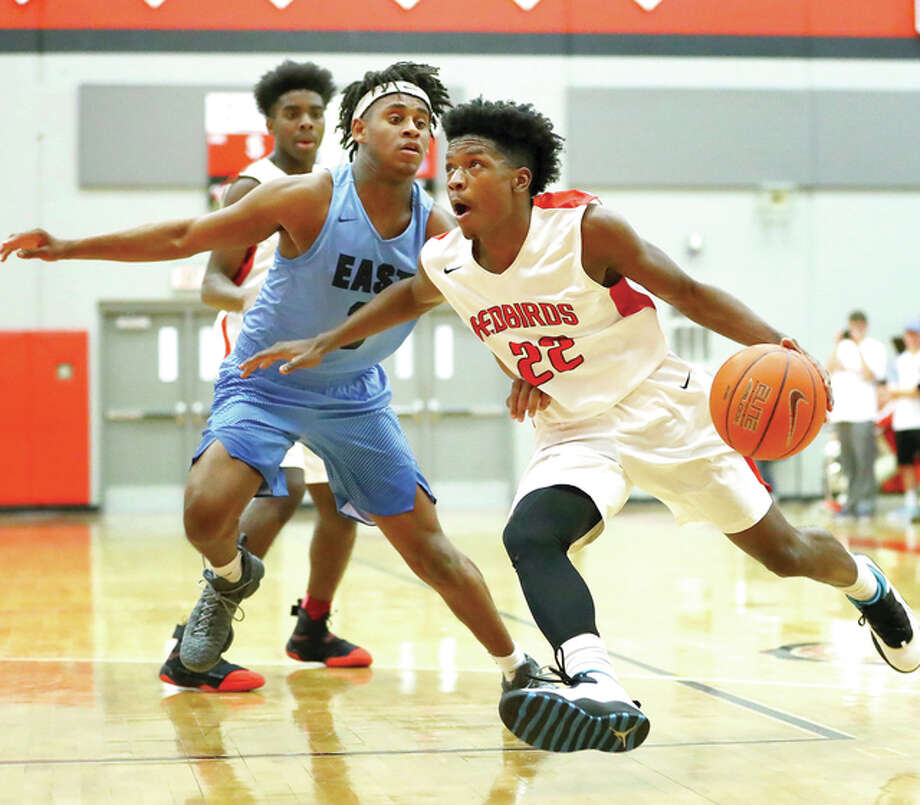 Alton's Kevin Caldwell, right, drives to the hoop past Belleville East's EnRico Sylvester during Friday night's game at Alton High School. Photo: Billy Hurst | For The Telegraph