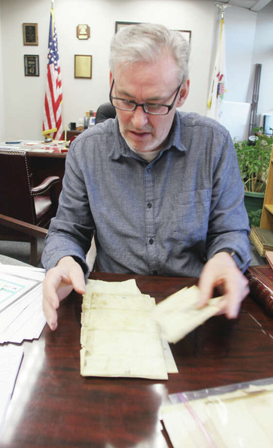 Madison County Circuit Clerk Mark Von Nida looks over old documents collected by office staff. Since discovering court documents relating to Elijah P. Lovejoy, he said they have been taking a closer look at documents being prepared for destruction.