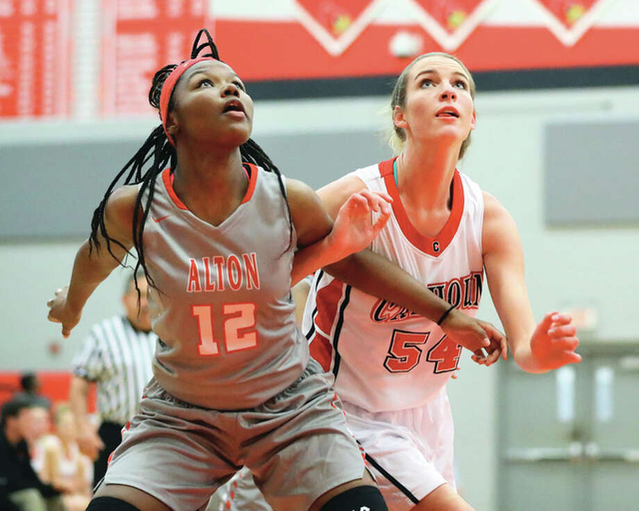 Alton's Leilani Hill (left) and Calhoun's Grace Baalman battle for a rebound during a Warriors victory Nov. 16 at the Alton Tourney. Calhoun, the defending Class 1A state champion, opens postseason play as the top seed at the Greenfield Class 1A Regional. Photo: Billy Hurst / For The Telegraph