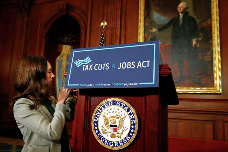 "Jacquelyn Martin | AP A House staff member affixes a sign that says ""Tax Cuts and Jobs Act"" ahead of a gathering of House Republicans making statements to the media following a vote on the GOP tax overhaul bill on Capitol Hill in Washington."