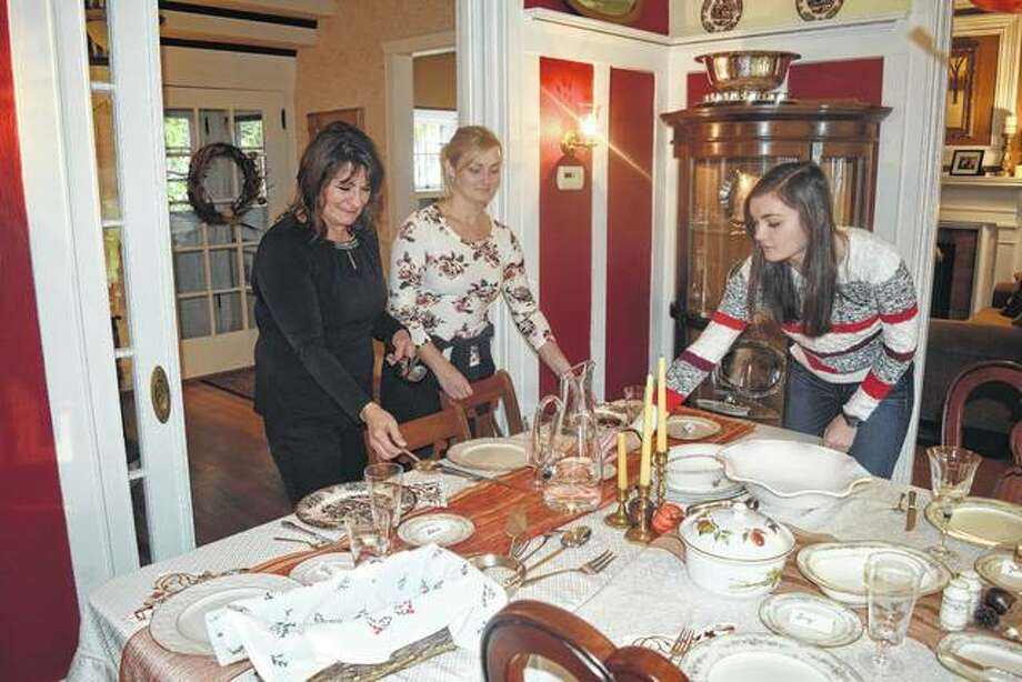 Kathy Langdon (from left) and her daughters, Rachel and Marie, set the dining room table Wednesday in preparation for today's Thanksgiving meal.