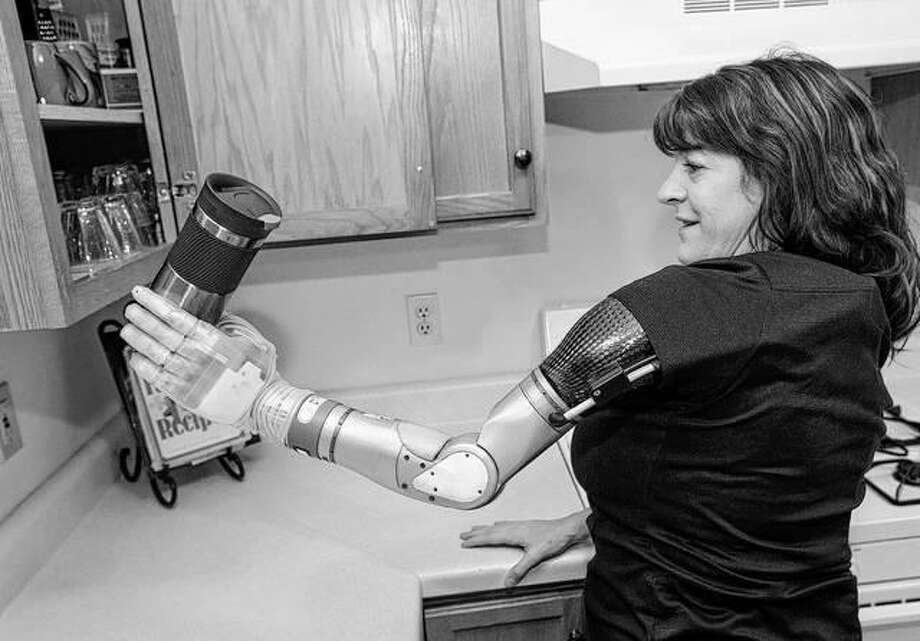 Army veteran Carrie Krischke uses her new robotic arm to get a coffee mug from her cupboard in Byron. Krischke lost her arm in the mid-1990s and she is learning to adapt with a body-powered prosthetic.