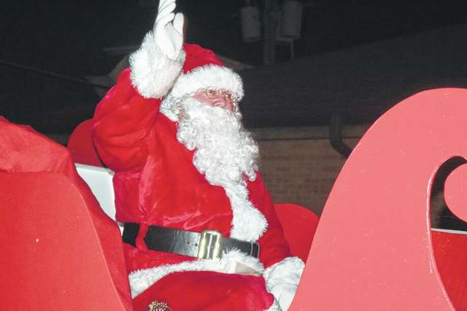 Santa Claus waves to the crowd as his sleigh pulls onto the Beardstown square Saturday during the ninth annual Nighttime Christmas Parade. Photo: Greg Olson | Journal-Courier