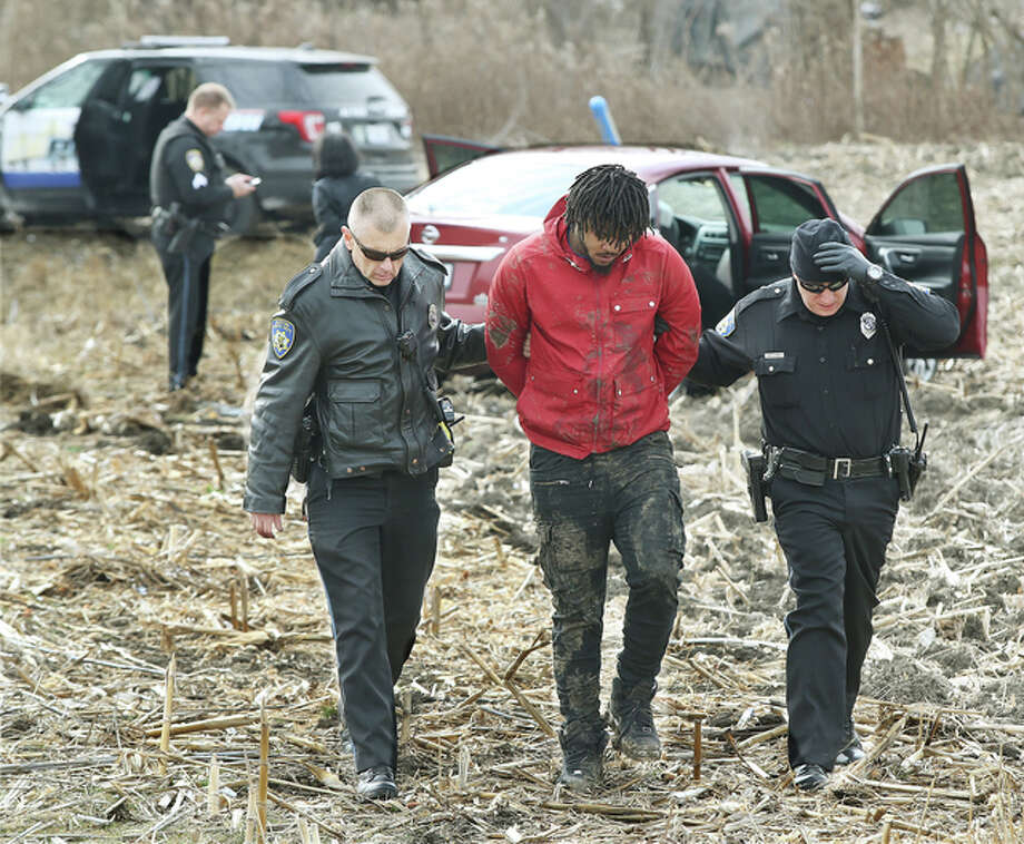 Officer David Penney, left, and Sgt. Jason Cole, right, escort a man taken into custody in connection with an alleged felony retail theft from the Alton J.C. Penney store Thursday after a high-speed chase into Missouri, where the vehicle the suspect was riding in crashed into a pickup truck. A female with him was also handcuffed but was injured in the crash, and transported by ambulance from the scene. The woman had been driving the car.