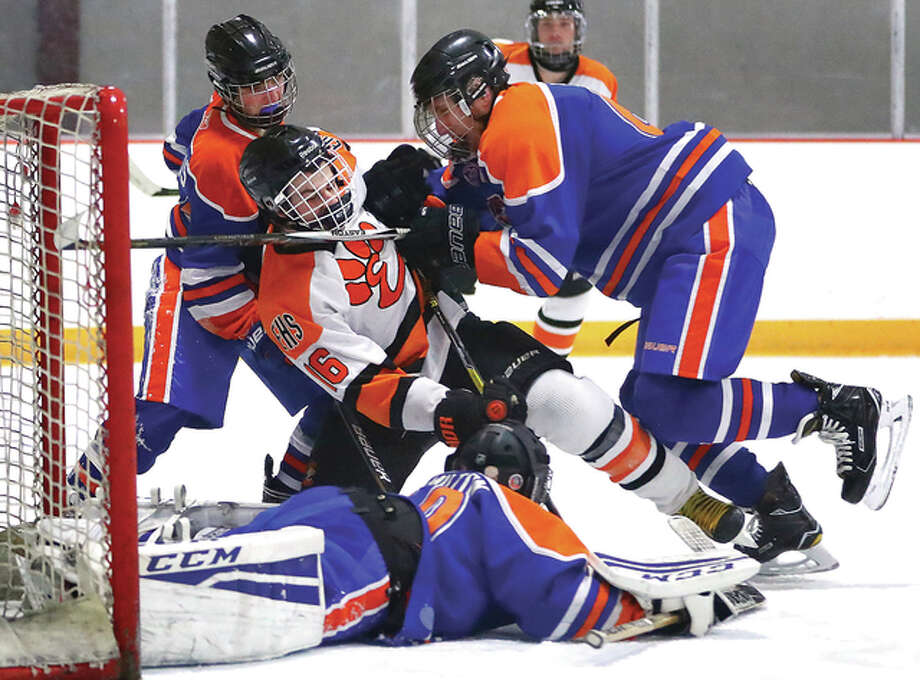 Edwardsville's Kellen Roettgers, top middle, is knocked to the ice by Freeburg/Waterloo's Austin Patton, right, while goalie Peyton Hamilton makes a save as Braden Fiscus, top left, looks on during Game 1 of the MVCHA 2A semifinals Thursday at the East Alton Ice Arena. Photo: Billy Hurst | For The Telegraph
