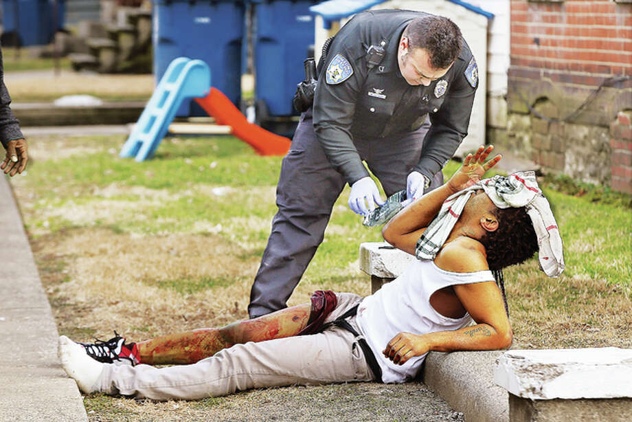 Alton Police officer Manuel Espinoza applies first aid to a man, 26, Friday afternoon who was screaming into a towel in pain after apparently being shot in the right leg. The act of violence appeared to be domestic from interviews with people from the residence, police said. The incident occurred at a residence in the 800 block of Fountain. No further information will be given out until charges are presented or investigation is complete. The man suffered non-life-threatening injury from the shot in the leg. Police found the man at the corner of Spring and Fountain streets bleeding profusely. Alton firefighters arrived and treated the man who was transported to a local hospital by LifeStar Ambulance Service. Who shot the man and how he ended up on the street corner was under investigation Friday evening by Alton Police detectives. The general neighborhood where the man was found has been the location of several gun-related incidents in recent months, one just one block away where a pickup truck was struck by bullets several times during a shooting.