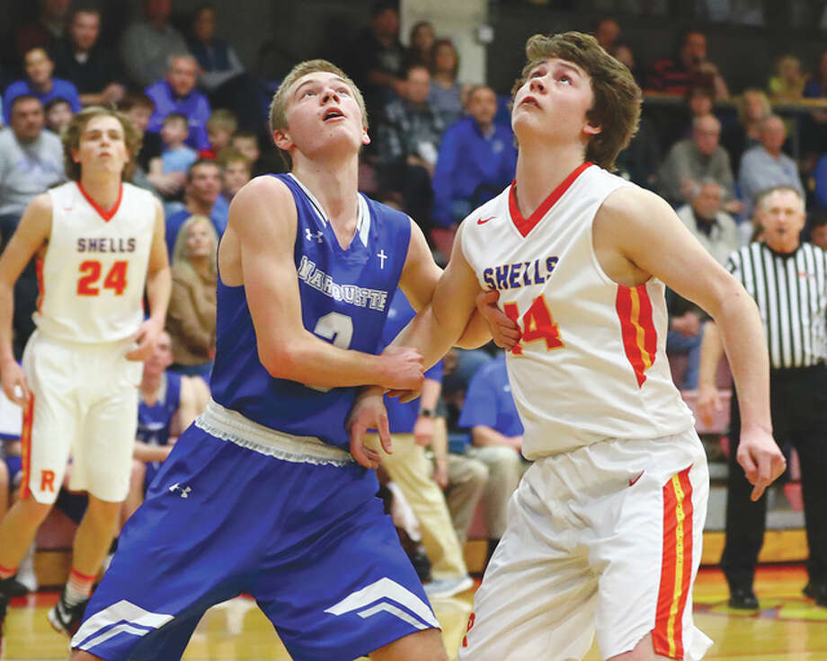 Marquette's Sammy Green, left, and Roxana's Brayden Davis battle for position on a rebound during Friday night's game at Larry Milazzo Gymnasium in Roxana. Marquette won 63-23. Photo: Billy Hurst   For The Telegraph