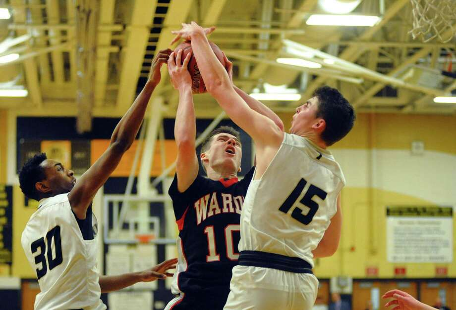 Fairfield Warde's Sean Conway is fouled by Trumbull's Chris Brown as he attempts a shot during basketball action in Trumbull, Conn., on Friday Feb. 9, 2018. Defending at left is Trumbull's Timmond Williams. Photo: Christian Abraham / Hearst Connecticut Media / Connecticut Post