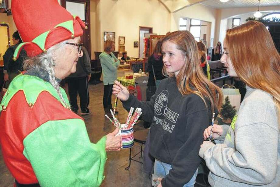 Janis Dappert (left) hands out holiday pencils to Reagan Evans (center) and Madison DeJaynes, both of Winchester, on Saturday at the Old School Museum in Winchester during the annual Hometown Christmas event. Photo: Greg Olson | Journal-Courier