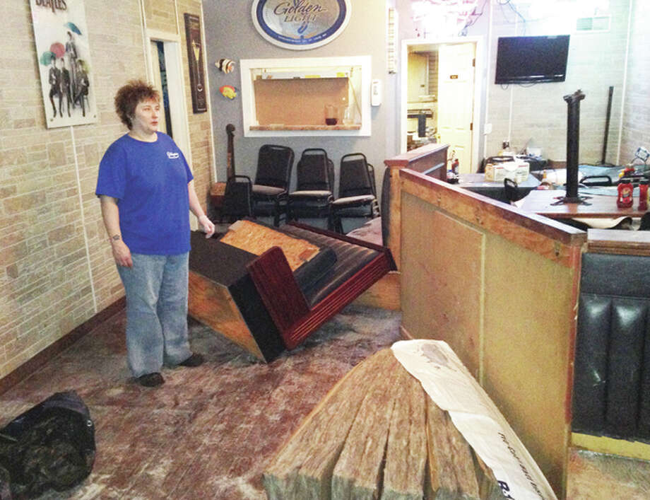 Terri Michki, a co-owner of Gilliganz Bar and Grill, surveys damage to the dining room Tuesday, the day after a regular customer accidentally drove a pickup through the wall into the room. No injuries were reported and repairs should be completed in a few days.