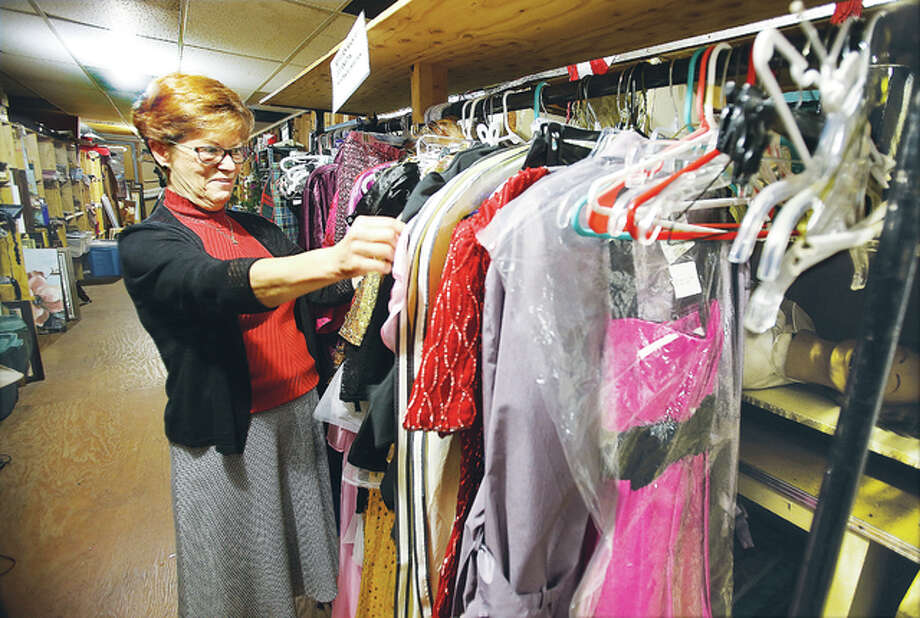 Diana Enloe, looking through some wardrobe in the extensive props department at Alton Little Theater, is retiring after nearly 40 years of directing Illinois' longest-running community theater.