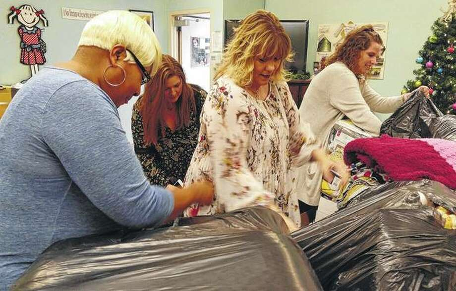 New Directions Director Vanessa Tyus, Jacksonville Area Convention and Visitors Bureau Director Brittany Henry, Hampton Inn General Manager Michelle Foreman and JACVB employee Paige Graham unpack the blankets donated from the community the New Directions on Monday.