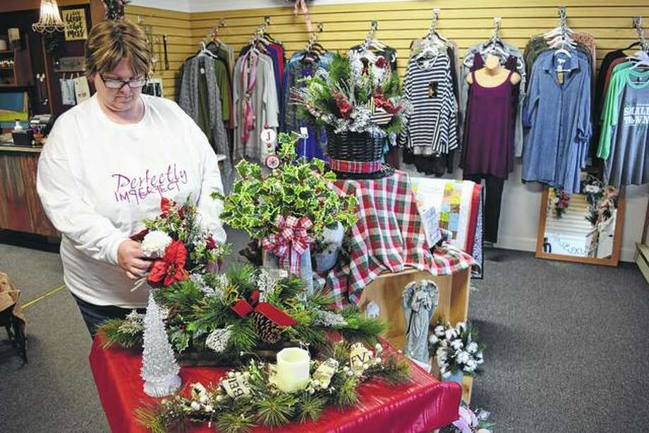 Stacee Rohn of Hersman arranges some items in her new shop, Perfectly Imperfect Gifts and More, in Mount Sterling.