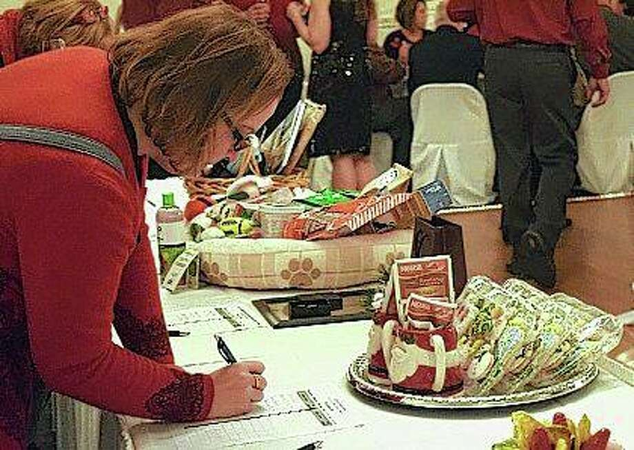 Kristan Becker Hoffman places a silent bid Tuesday during the Governor Duncan Association Holiday Gala at Hamilton's. Photo: Samantha McDaniel-Ogletree   Journal-Courier