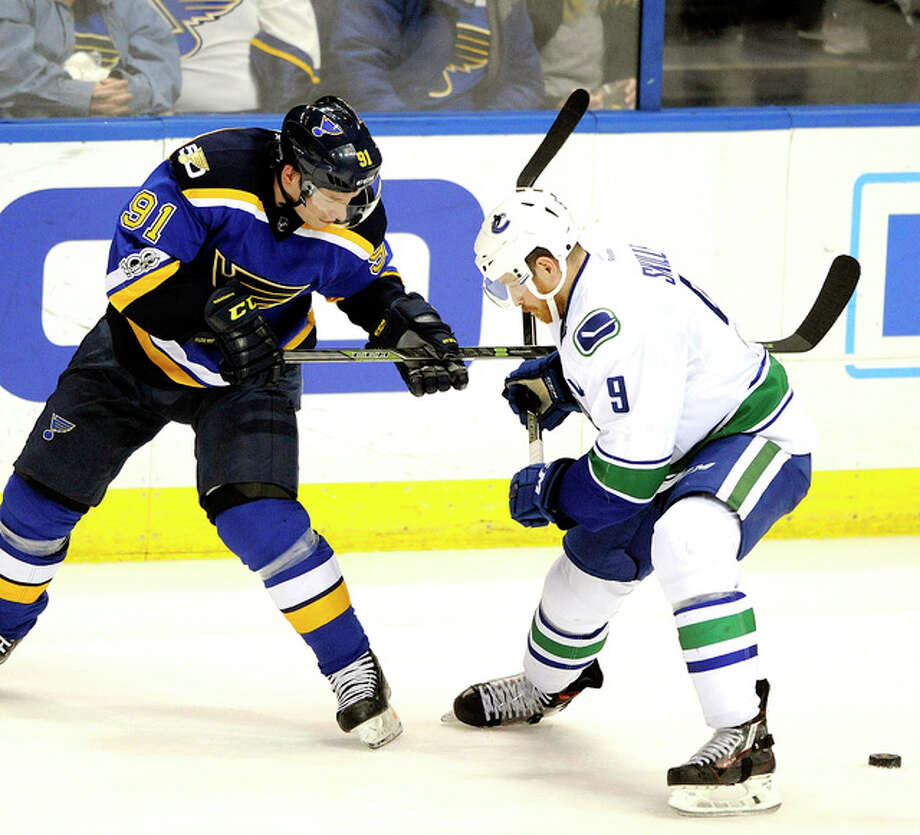 The Blues' Vladimir Tarasenko (91) and Vancouver's Jack Skille (9) reach for the puck Thursday in St. Louis. Photo: AP
