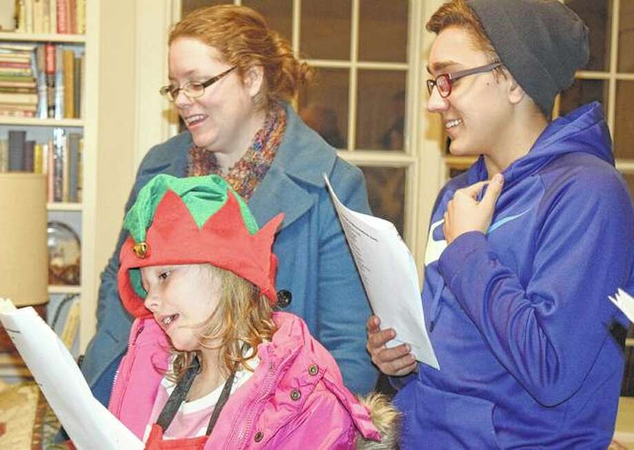 Siobhan Warren (left), her daughter Hannah Warren and Carlos Rubin de Celis sing Christmas carols Friday at a home on West Lafayette Avenue. The group from First Presbyterian Church sang carols for residents at Heritage Health, Cedarhurst and the homes of family and friends.