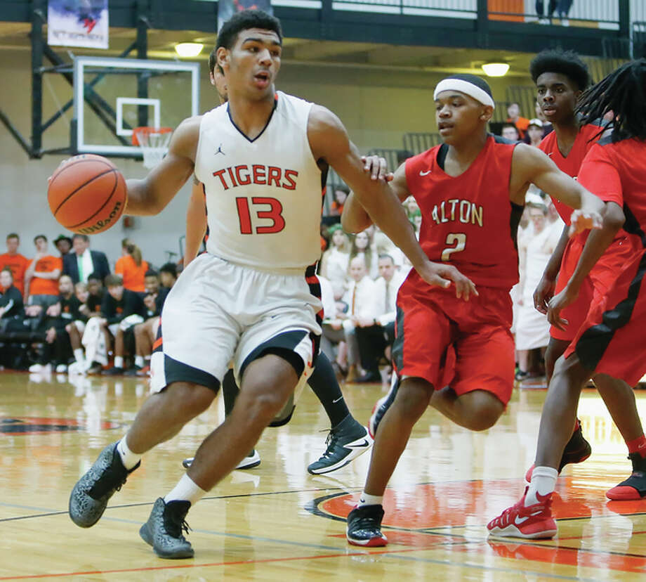 Edwardsville's Mark Smith (left) drives past Alton's Ty'ohn Trimble during the Tigers' Southwestern Conference victory over the Redbirds on Friday night at Lucco-Jackson Gym in Edwardsville. Photo: Scott Kane / For The Telegraph