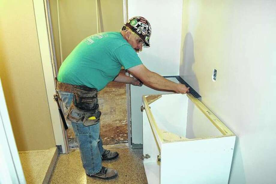 Tony Dippel, a carpenter with R.D. Lawrence Construction Co., sets a bathroom vanity in MacMurray College's Jane Hall, a dormitory that is under renovation.