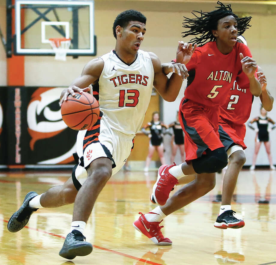Edwardsville's Mark Smith (left) drives to the basket while Alton's Donovan Clay pursues the play during the Tigers' Southwestern Conference boys basketball victory Friday night a Lucco-Jackson Gym in Edwardsville. Photo: Scott Kane / For The Telegraph