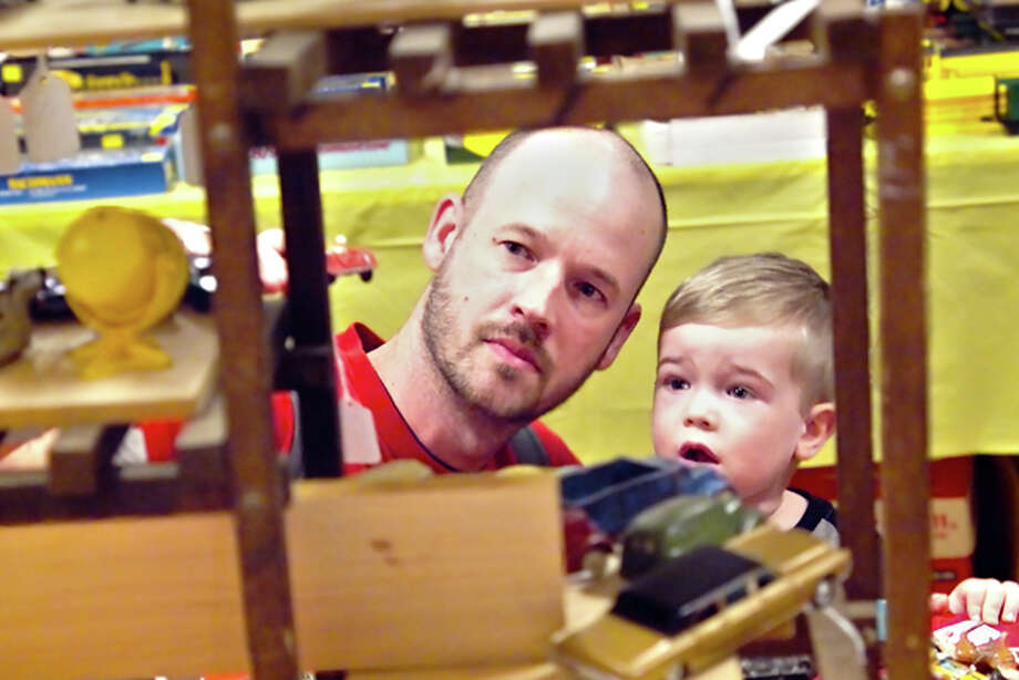Shawn Cozart and his 2-year-old son Hayden, of Glen Carbon, inspect a collection of antique die-cast toys Saturday during the Alton Train Show, held annually at the Franklin Masonic Lodge in Alton. It was their first time attending the show, and Shawn noted his son's immediate interest in trains and old-fashioned toys.