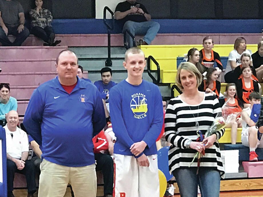 Roxana High School senior, Zach Golenor, center, is pictured with his parents, Jim and Debby Golenor, at RHS's Senior Night last Friday. Zach broke the RHS all-time record for being the second-highest scoring student in his four-year athletic career to make 1,418 points. Photo: For The Telegraph