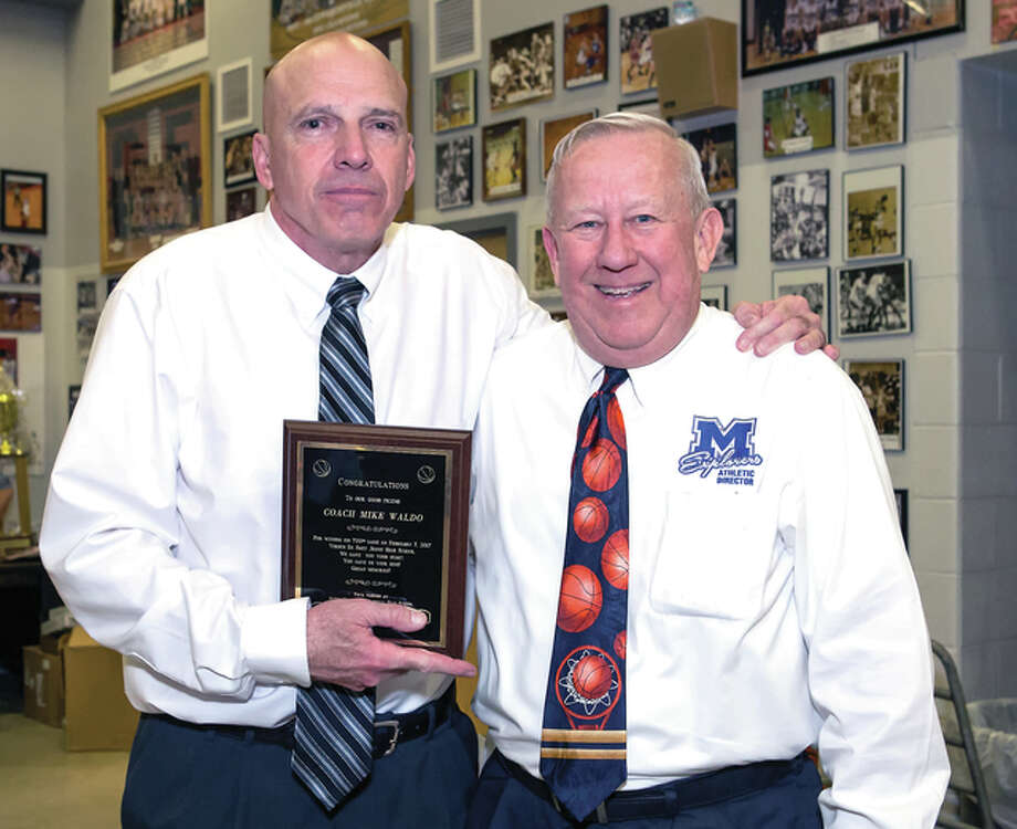 Edwardsville High basketball coach Mike Waldo, left, accepts a plaque from Marquette Catholic High AD Jack Holmes in recognition of Waldo's 700th career victory earlier this season. Wado began his coaching career at MArquette and his first 87 victories (and first regional title) came as the Explorers' coach. Photo: Submitted Photo