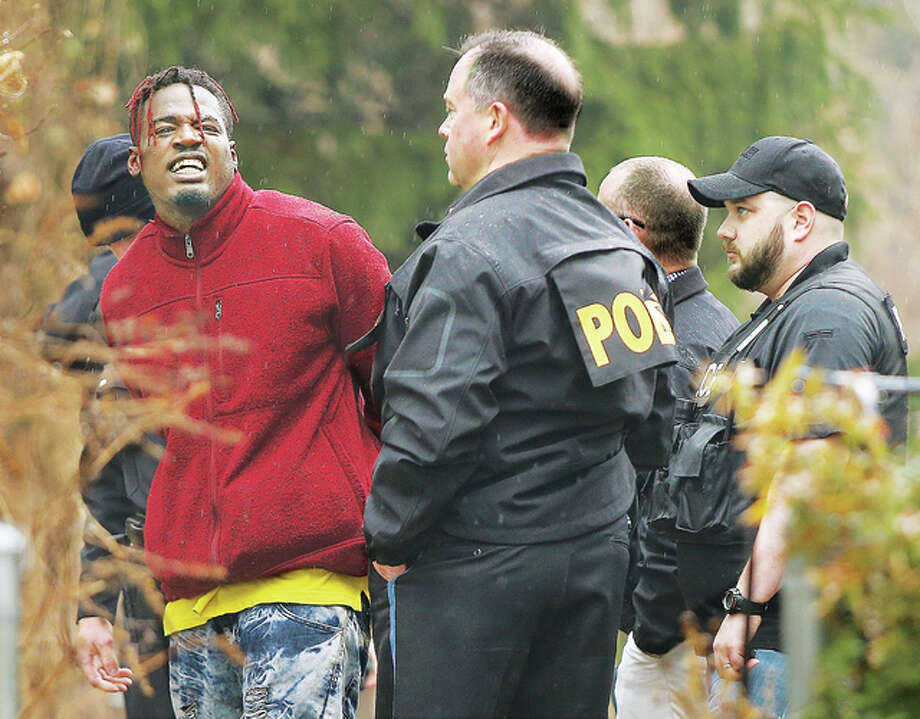 A man, left, who bragged about being a registered sex offender, shouts obscenities at a news photographer Tuesday after being arrested following a chase through the woods behind the Calvary Baptist Church in Alton. The man was chased and arrested by officers on foot, with help from a canine unit, within about 20 minutes of the robbery of the U.S. Bank branch nearby at the corner of Brown Street and Washington Avenue. The man, apprehended behind a house in the 1200 block of Washington Avenue, was wearing different clothing than the description of the robbery suspect, but police later located evidence in the woods where the chase had occurred. The FBI has joined the investigation with the Alton Police Department. Photo: John Badman | The Telegraph