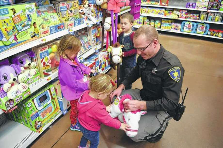 Annie Armstrong, 2, (clockwise from left), Halle Armstrong, 4, Ryder Armstrong, 5, and Morgan County Sheriff's Deputy Leo Peterson look at toys Saturday at Walmart during the sheriff's deputies' annual Christmas program. The Armstrong siblings are the children of Evan and Katie Armstrong of Jacksonville.