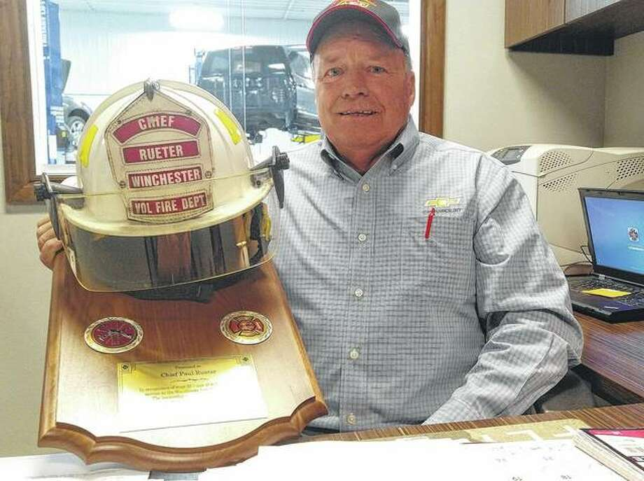 Outgoing Fire Chief Paul Rueter shows a plaque given to him by the Winchester City Council to commemorate his years of service.