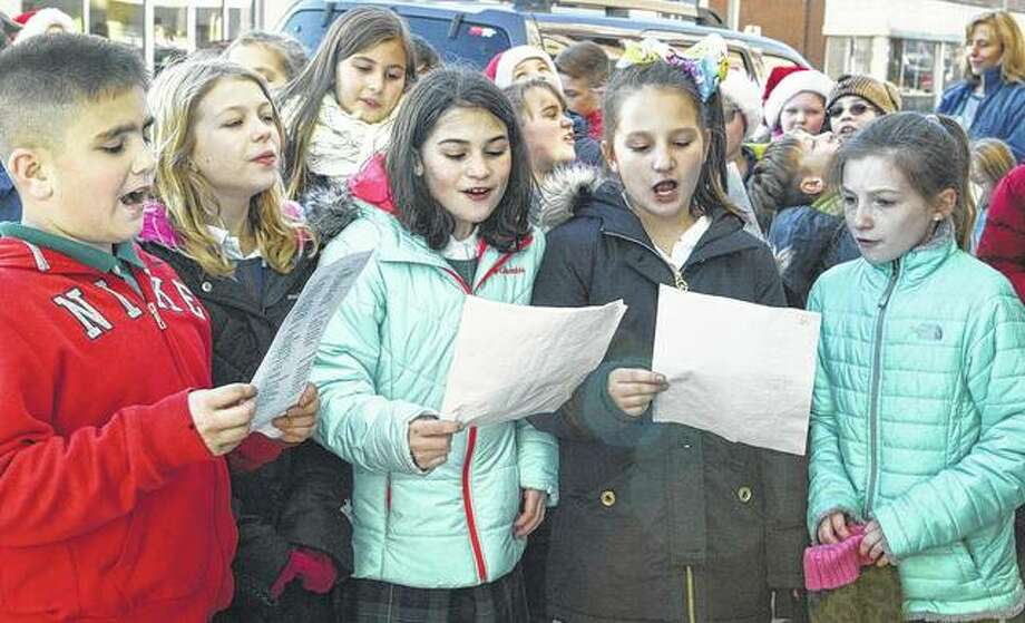 "Our Saviour School fourth-graders Dominick York (from left), Clarissa Emerick, Sophie Cole, Angelique Lowery and Kendall Little sing ""Frosty the Snowman"" while the group was caroling Wednesday along West State Street."