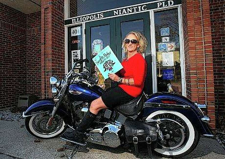 "In this Dec. 5, 207 photo, librarian Shelley Hopkins poses with her Harley-Davidson motorcycle fondly dubbed ""Rayce,"" outside the Illiopolis/Niantic Public Library with one of her favorite books in Illiopolis, Ill. Rayce (pronounced ray-see) is one of the reasons Hopkins, who celebrated her 25th anniversary as librarian on Dec. 4, said she is not a stereotypical librarian. ""Librarians are quiet,"" Hopkins said. She jokingly says her voice and her laugh are loud, and that's part of what makes her different from the image people have of librarians, and then there's the bike and her tattoos. (Jim Bowling/Herald & Review via AP)"
