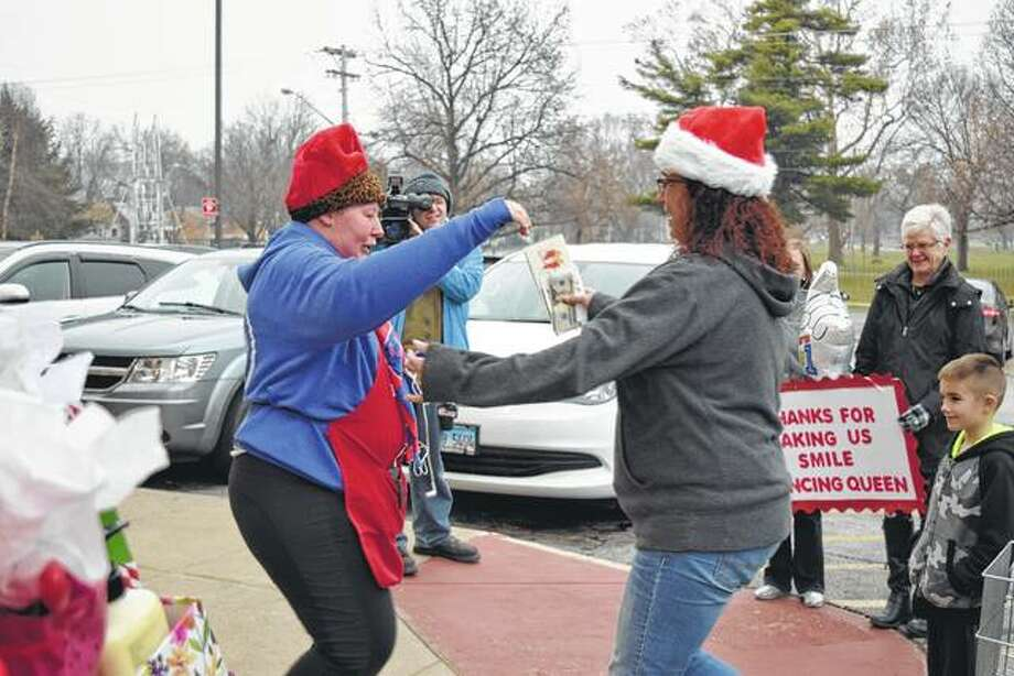 Nichole Busch (left) reaches out to hug Michelle York on Friday outside Walgreens after Busch was presented with a large number of gifts, including cash, to help her out this Christmas. Busch, who works a few jobs to make ends meet, is known in Jacksonville as the dancing employee of Liberty Tax Service and Sun Loan. Photo: Greg Olson | Journal-Courier