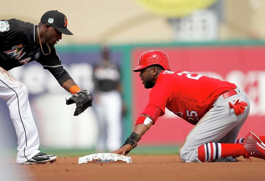 The Marlins' Adeiny Hechavarria tries to tag out Dexter Fowler of the Cardinals during a spring training game Saturday at Roger Dean Stadium in Jupiter, Fla. Photo: AP