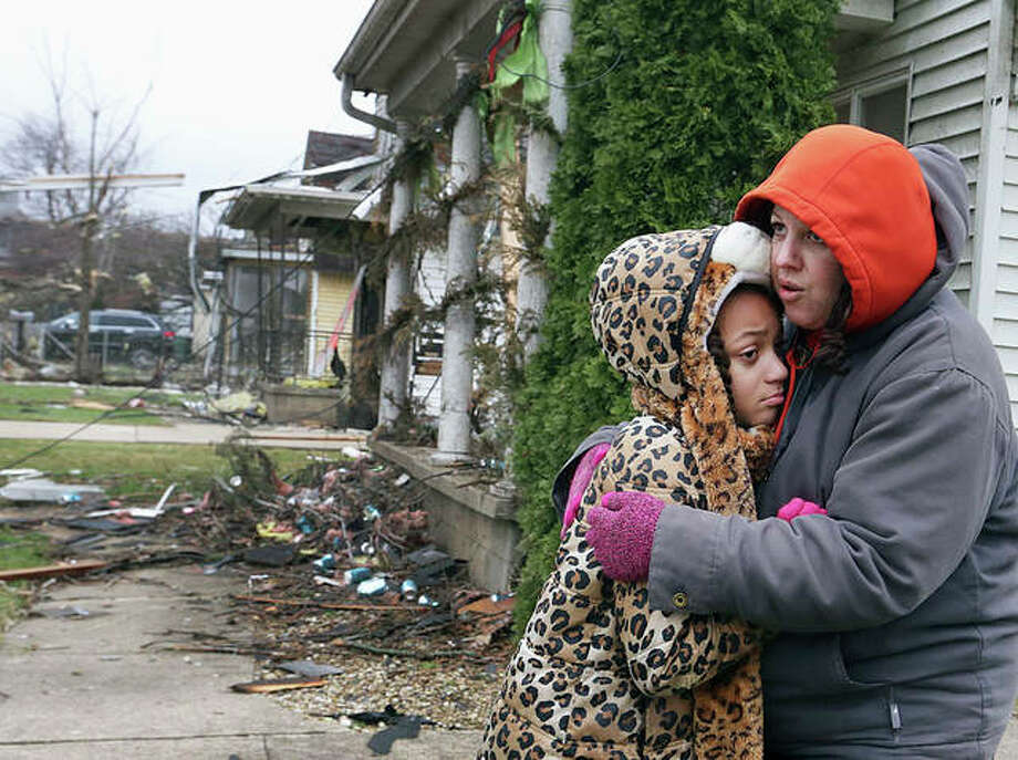 Scott Anderson | NewsTribune (AP) Valerie McAvoy hugs her daughter, Olivia, on Wednesday after their home in Naplate was destroyed by a tornado Tuesday evening. About 50 houses had damage in the town.