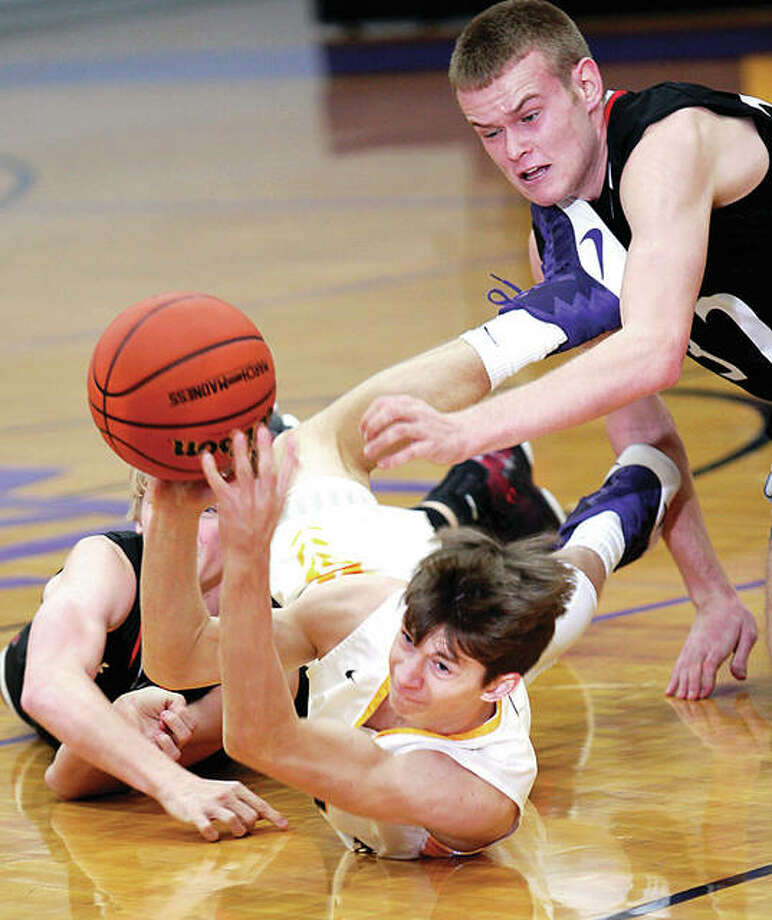 Civic Memorial's Caden Clark slips between Triad's Noah Moss, left back, and Kyle Rood, right to recover a loose ball in Wednesday night's overtime win over Triad in the Class 3A Regional semifinals at CM. Clark got the ball to teammate Will Buhs, who scored a basket on the play. Photo: James B. Ritter | For The Telegraph