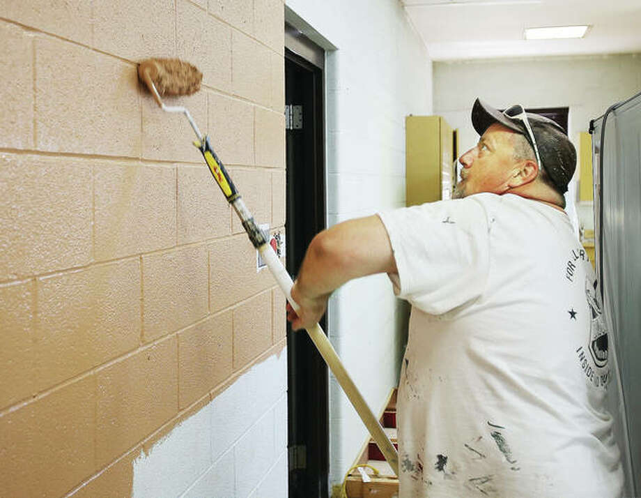 John Badman|The Telegraph Jeff Masterson, of Daveco Painting in Wood River, rollers a fresh coat of paint on the walls of the common areas of the Wood River Fire Station Thursday. The entire station, except for the truck bay, is getting a fresh coat of paint, some new carpeting and floor tiles during a renovation.