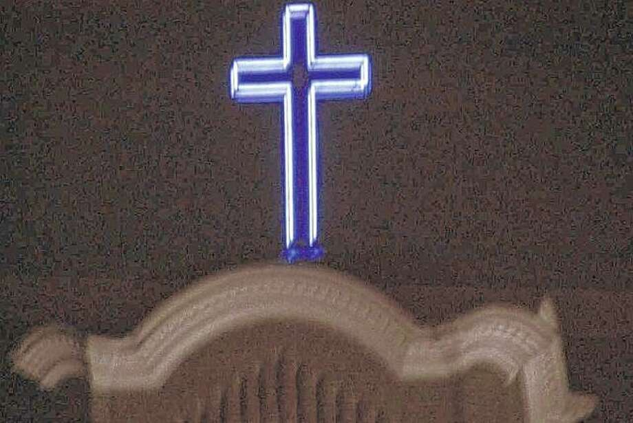 A cross glows from the top of a church in White Hall.