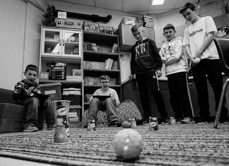 Second graders Urijah Burns (from left) and Eli Binkley play a remote controlled game with help from eighth graders Christian Schanefelt, Joey Young and Austin Cohn from Warrensburg-Latham Middle School at the elementary school in Warrensburg. The middle school students at Latham spend time playing games with elementary school students for their kindness project.