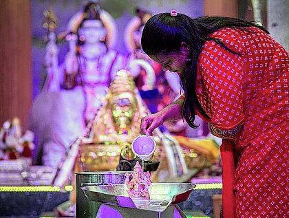 Sandhya Budhi makes an offering of milk, which is a symbol of purity, to the Deity Ganesha as Hindus gather at the Hindu Temple of Central Illinois in West Peoria. Sitting on 25 acres atop a high bluff, the temple space presents multiple deities, which the faithful use to help focus their meditation. Fred Zwicky   Journal Star (AP)