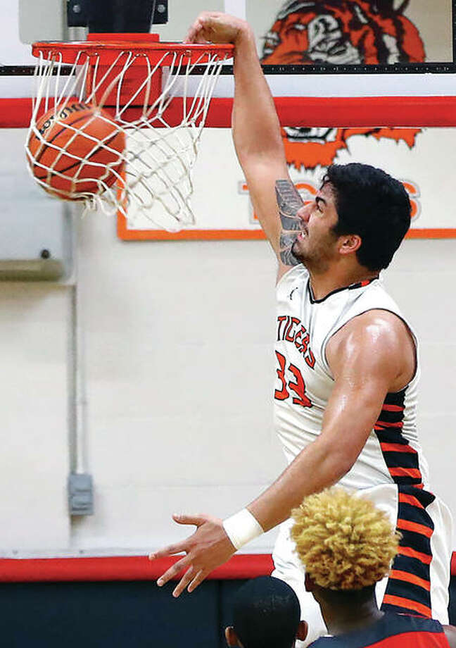 Edwardsville's A.J. Epenesa throws down a slam dunk in Friday night's regional championship game win over Alton at Granite City. Photo: Billy Hurst | For The Telegraph