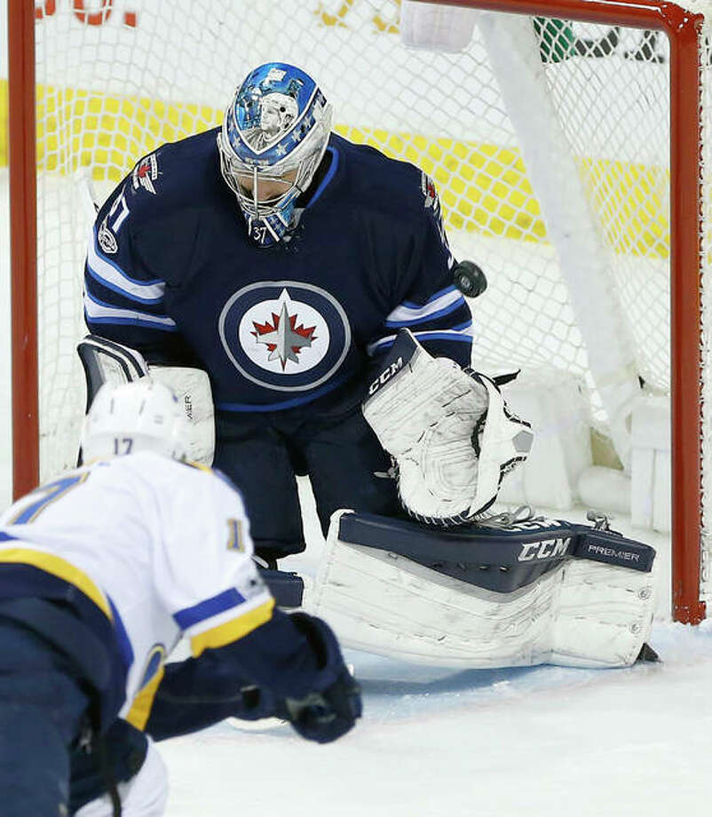 Winnipeg Jets goalie Connor Hellebuyck (37) saves the shot by the Blues' Jaden Schwartz (17) Friday night in Winnipeg.