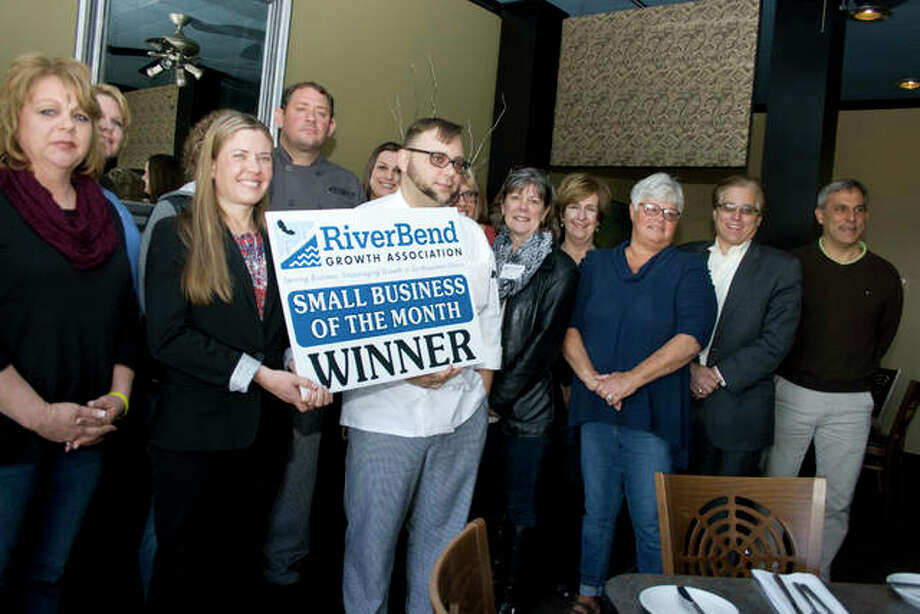 Local dignitaries, including Alton Mayor Brant Walker, second from the right, gathered at Gentelin's for the announcement it had been chosen as Small Business of the Month for March. Sarah Gentelin, holding the sign, co-owns the business with Ryan Gentelin, who stands behind her.