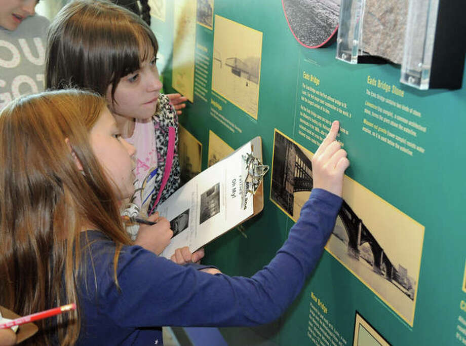 Girl Scouts identify bridges in the exhibits at the National Great Rivers Museum on Saturday during the Building Bridges Merit Badge session.
