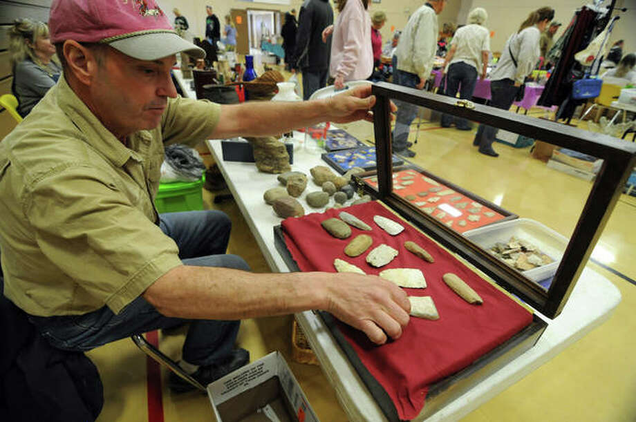 Brad Mullen, of Bunker Hill, arranges Native American artifacts he sold Saturday.