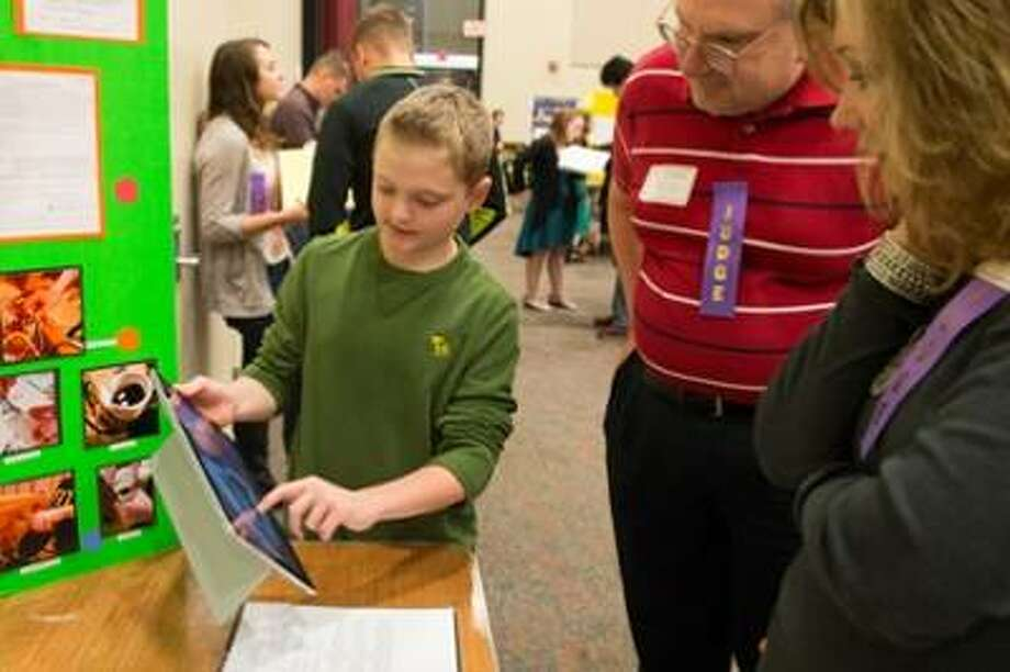 A student presents his STEM-focused project to a pair of judges during the Science Engineering Research Challenge held at SIUE. Photo: For The Telegraph