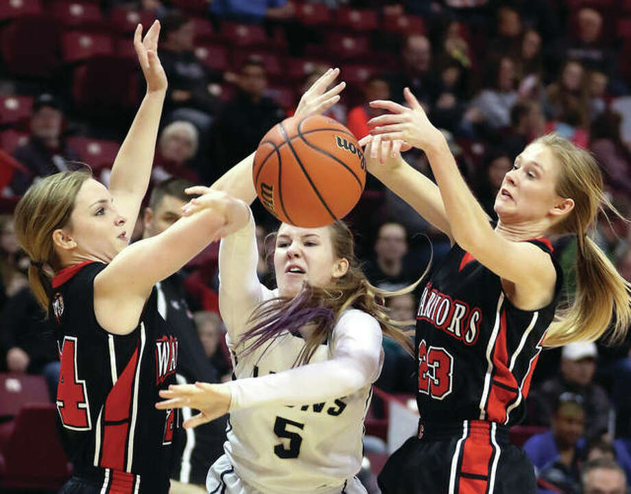 Elgin Harvest Christian's Jenn Kasper looses possession of the basketball while being trapped by Calhoun's Emily Baalman (left) and Junie Zirkelbach (right) during the third-place game of the Class 1A girls basketball state trouanment on Feb. 25 at Redbird Arena in Normal. Photo: Associated Press