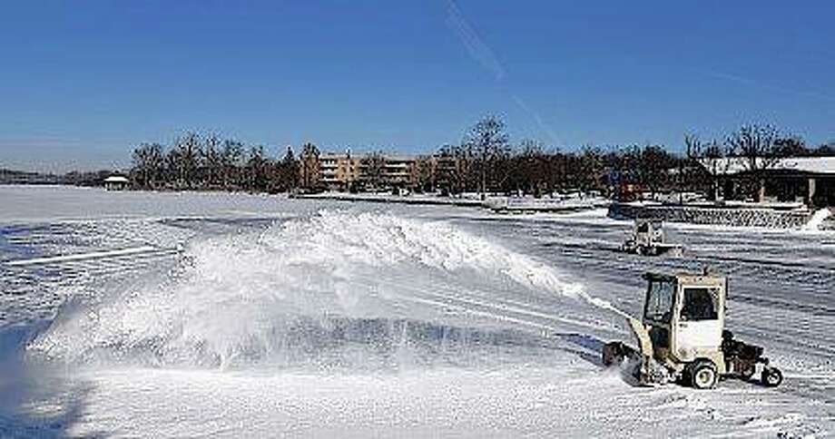 Workers clear off the snow from Depot Pond in Batavia to prepare for a skating area as frigid temperatures impact residents of Illinois. Rick West | Daily Herald (AP)