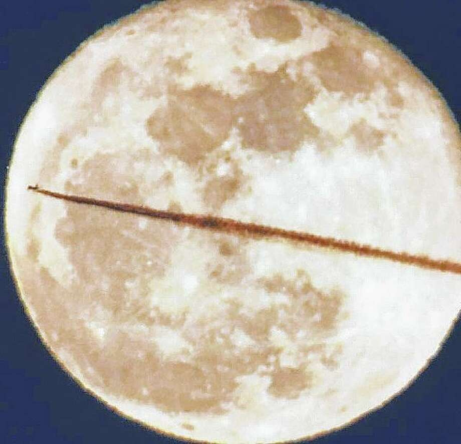 The vapor trail from a jet seems to cut a slice through the full moon.